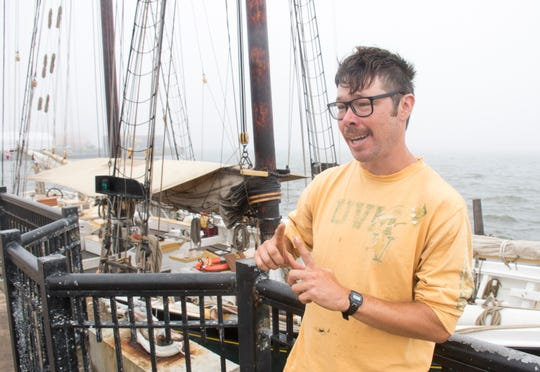 Tripp Seaman, a crew member on board the Lettie G. Howard, talks Wednesday about the historic ship docked in downtown Pensacola. The fishing schooner was built in 1893 in Essex, Massachusetts, and in 1901, the E. E. Saunders Co. of Pensacola purchased it for fishing off Mexico's Yucatan Peninsula. Though it is not open for tours, the public can view the ship from Plaza de Luna until it leaves this weekend.