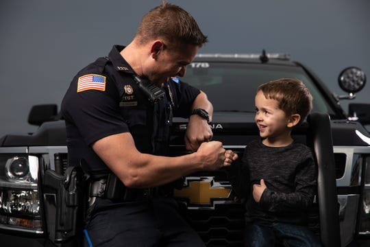 Pensacola police officer Stephen Grogan fist bumps his oldest son, Tristan.