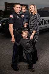 Pensacola police officer Stephen Grogan holds his youngest son, Camden, while posing for a photo beside his wife, Christina, and behind his oldest son, Tristan.