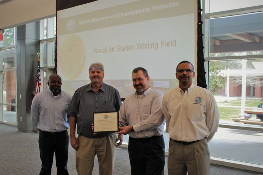 From left, Aaron Mitchell, Whiting Field interim water programs manager; Eddie Wright, Whiting Field water operator; Jeff Kissler, Whiting Field environmental director; and Shawn Hamilton, Florida Department of Environmental Protection Northwest District director, stand for a photo after the 2018 FDEP Plant Operations Award is presented to the installation.
