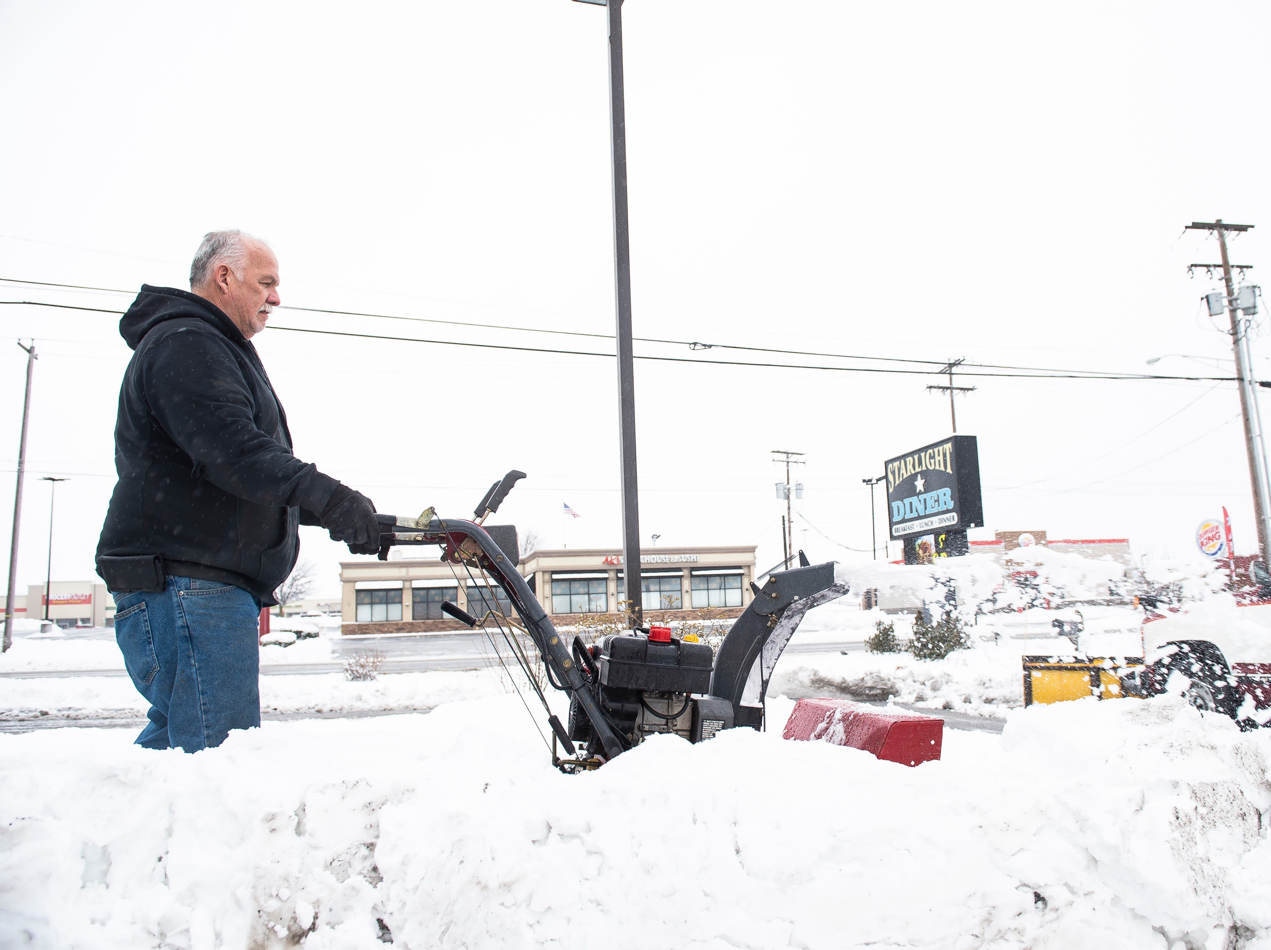 Dan Curry Sr. uses a snow blower to clear a sidewalk at the Starlight Diner as his son, Dan Curry Jr., plows snow in a pickup truck. Curry Sr. said he has been in the snow removal business for 25 years.