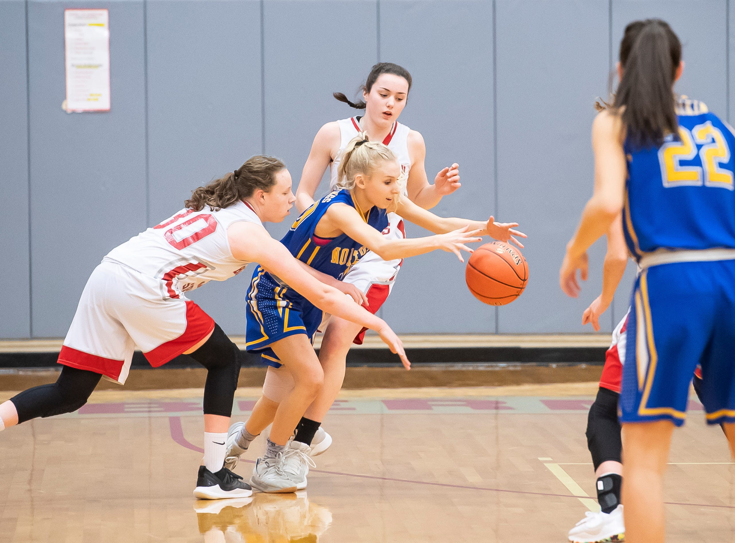 Northern Lebanon's Tabitha Hubbard, center, squeezes through a pair of Bermudian Springs defenders during play in the first round of the District III 4-A playoffs Tuesday, February 19, 2019. The Eagles won 58-52.
