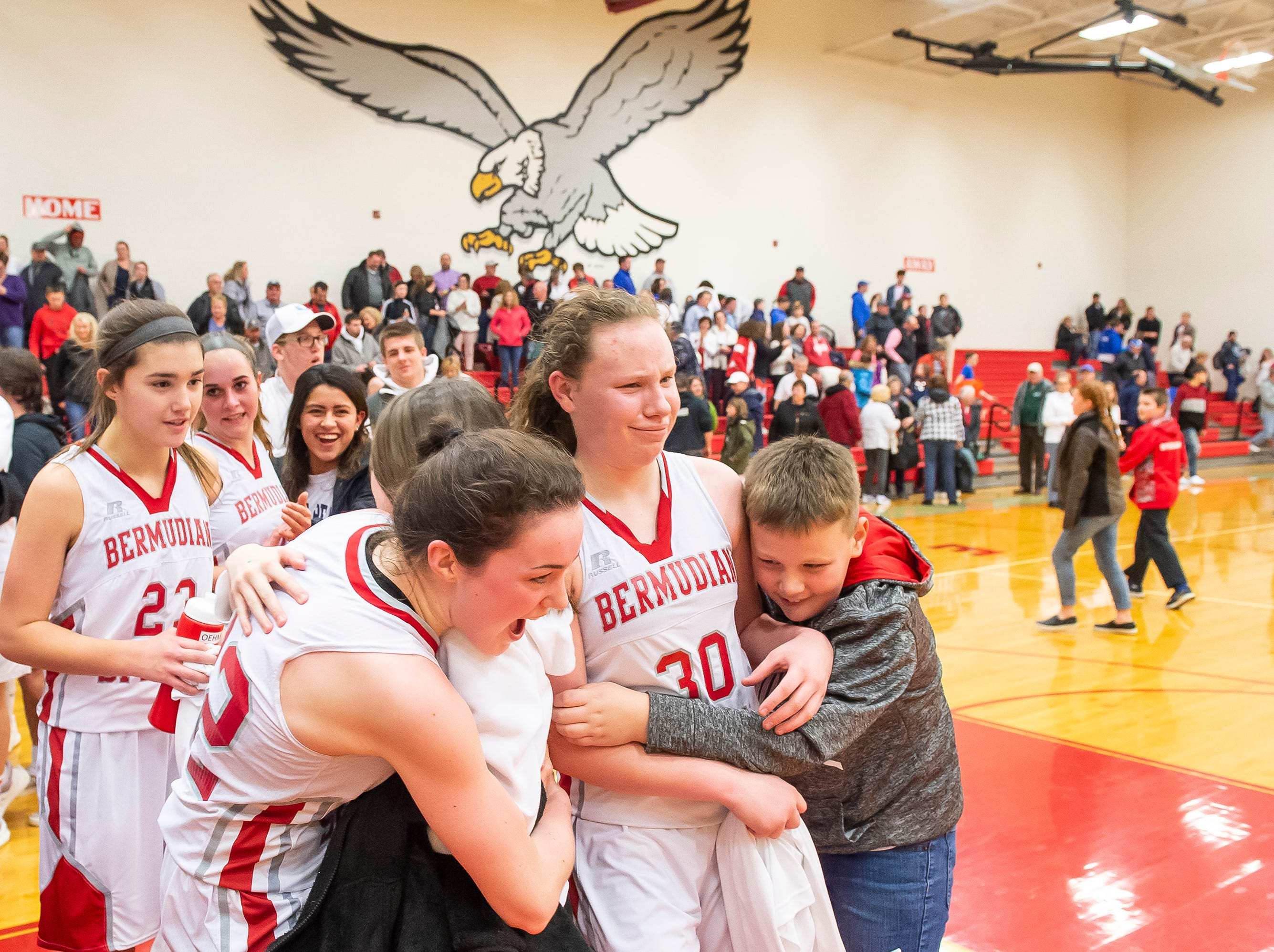 Bermudian Springs' Lillian Peters and Hannah Chenault (30) are greeted with hugs after defeating Northern Lebanon in the first round of the District III 4-A playoffs Tuesday, February 19, 2019. The Eagles won 58-52.
