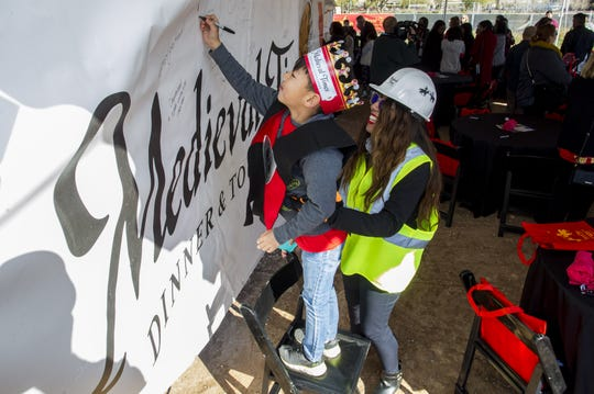 With the help of Synthia Feliciano, huge Medieval Times fan Ethan Smith, 7, of Peoria, signs a banner that will hang on a 120-foot steel beam inside the 10th castle coming to the Salt River Pima-Maricopa Indian Community's Talking Stick Entertainment District in Scottsdale, Feb, 20, 2019.