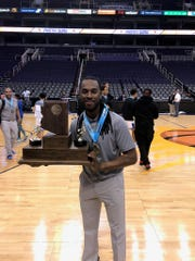 Eduprize coach Phil Lowe holds the CAA championship trophy.