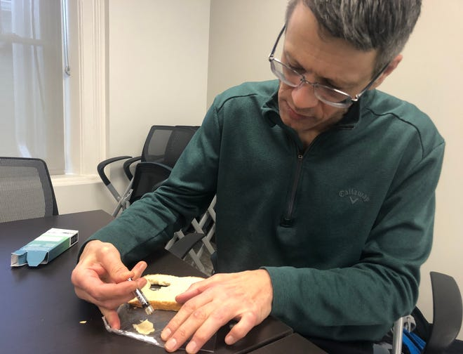 Peter DeVitis spreads some medical marijuana oil on to a piece of bread the afternoon of Tuesday, Feb. 19. DeVitis is one of about 80,000 residents in the state who started using the product since it was legalized a little under two years ago.