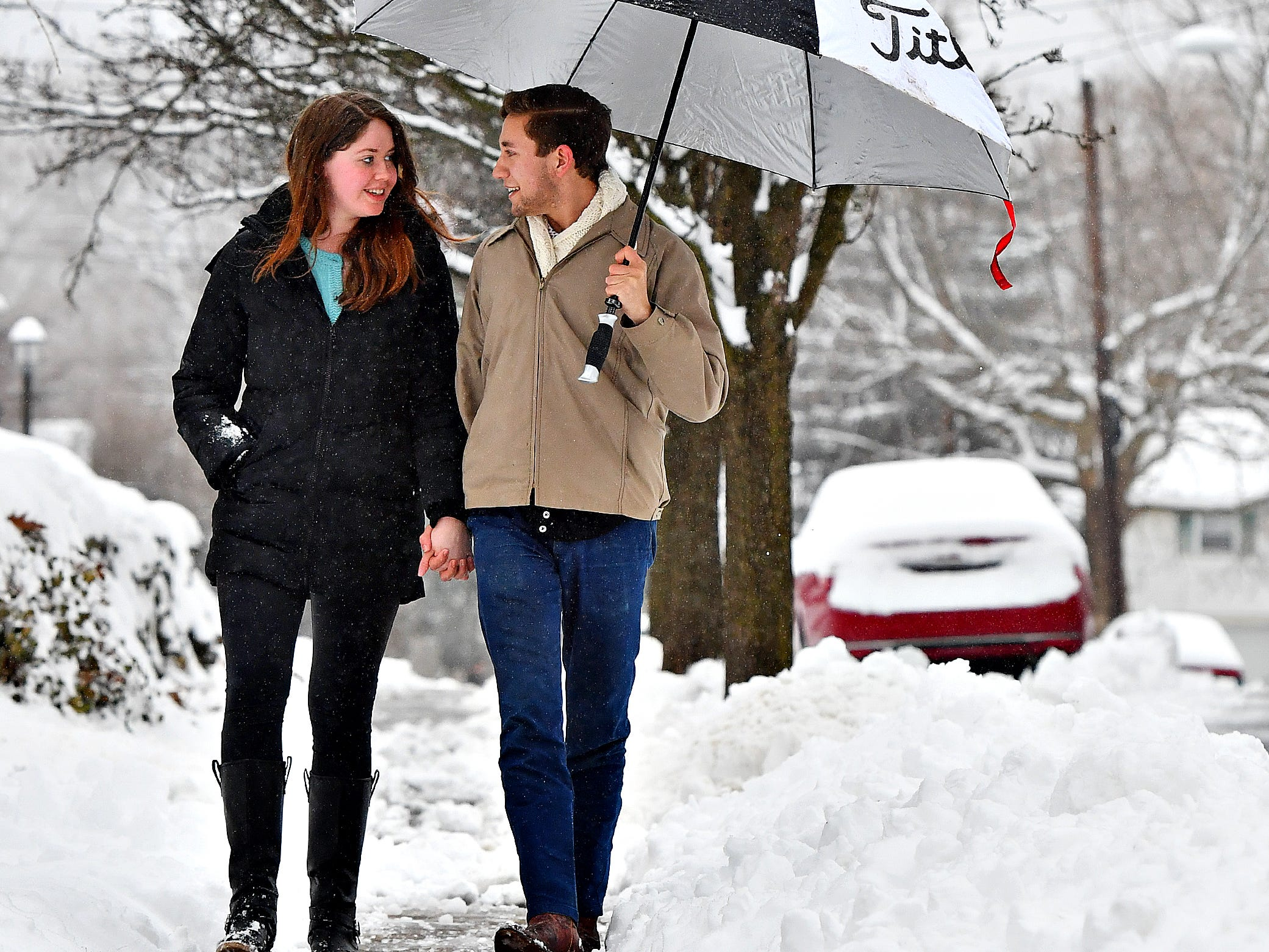 Ashton Howe, right, and Charli Muszynski, of Springettsbury Township, walk hand in hand while sharing an umbrella in the rain on North Keesey Street in Springettsbury Township, Wednesday, Feb. 20, 2019. Dawn J. Sagert photo