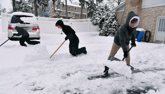 Carson Lehman, 14 at left, and brother Josh, 15, help neighbor Brennen Heinderer, 15, clear his driveway of snow on Forest Lane in Springettsbury Township, Wednesday, February 20, 2019.