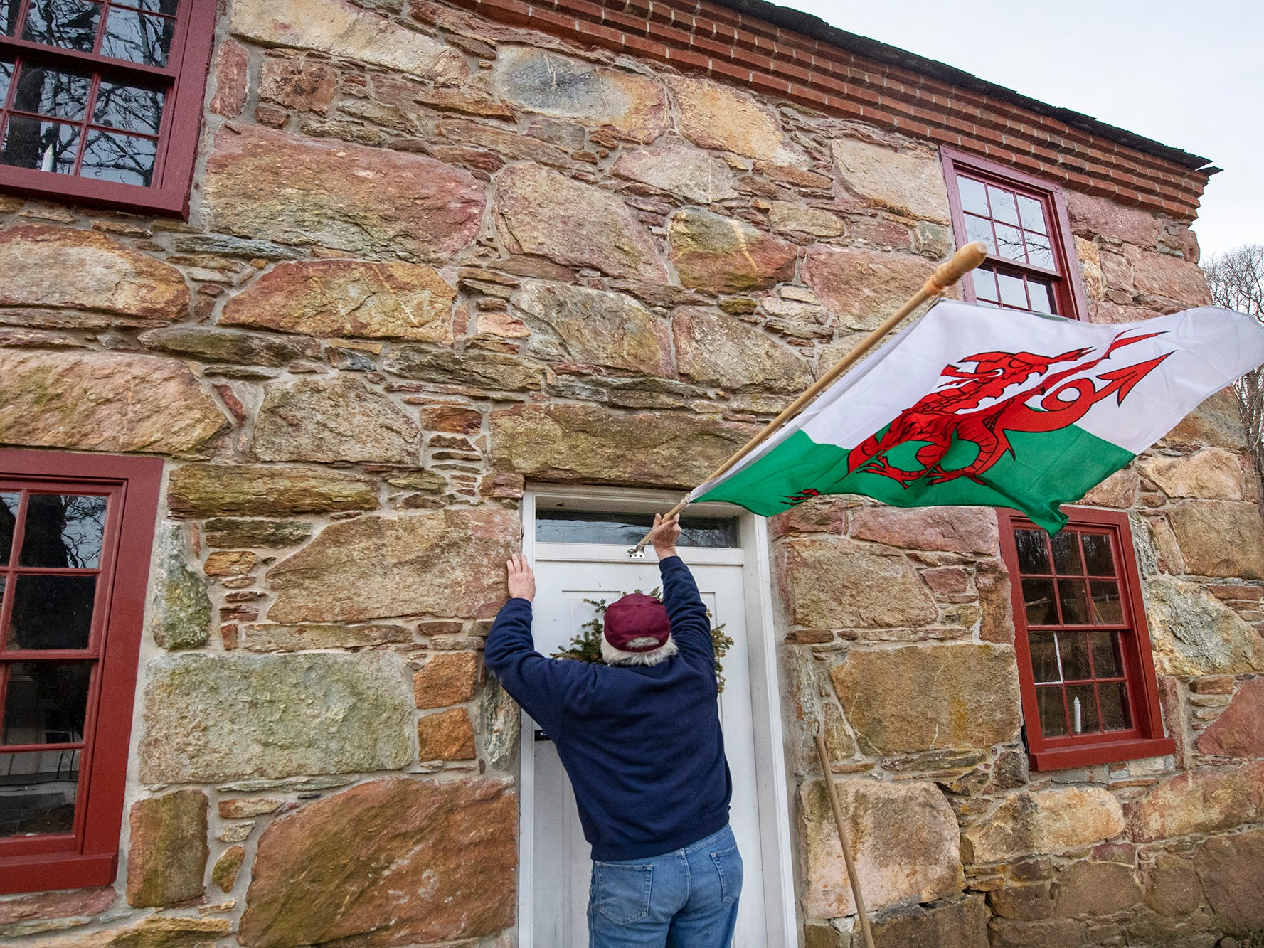 Don Robinson places a Welsh flag on one of the Welsh quarrymen's cottages in Peach Bottom February 19, 2019.