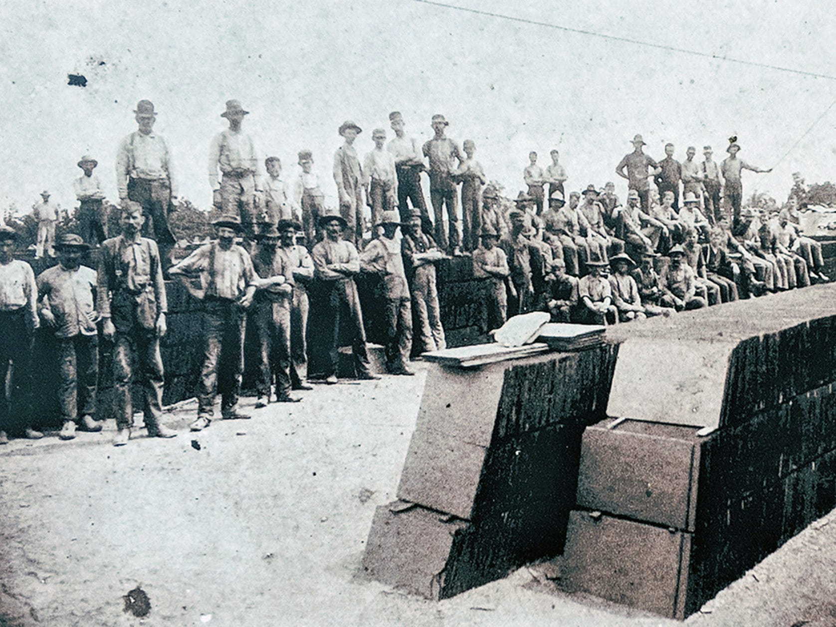 These are splitters, dressers, and quarryman at Proctor's Quarry around 1895. Note the stacked slates. This is known as a slate bank. The picture is mounted on an interpretive board in Coulsontown in front of the Welsh quarrymen's cottages.