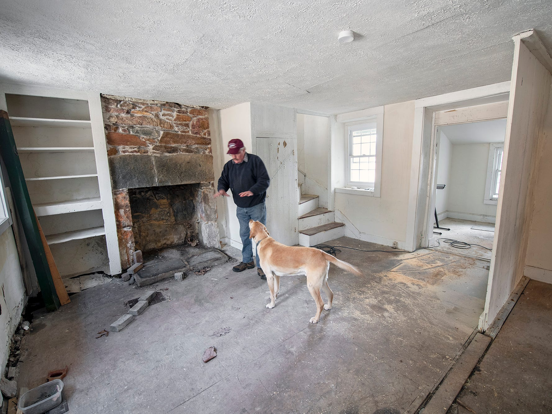 Don Robinson and his dog Jake stand next to the fireplace of the  recent Welsh quarrymen's cottage acquisition. He would like to return the original woodwork to the hearth.