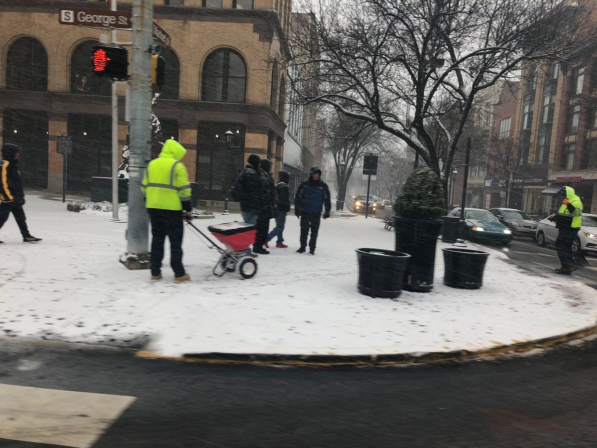 Workers prepare the sidewalks in downtown York as the snow falls Wednesday.