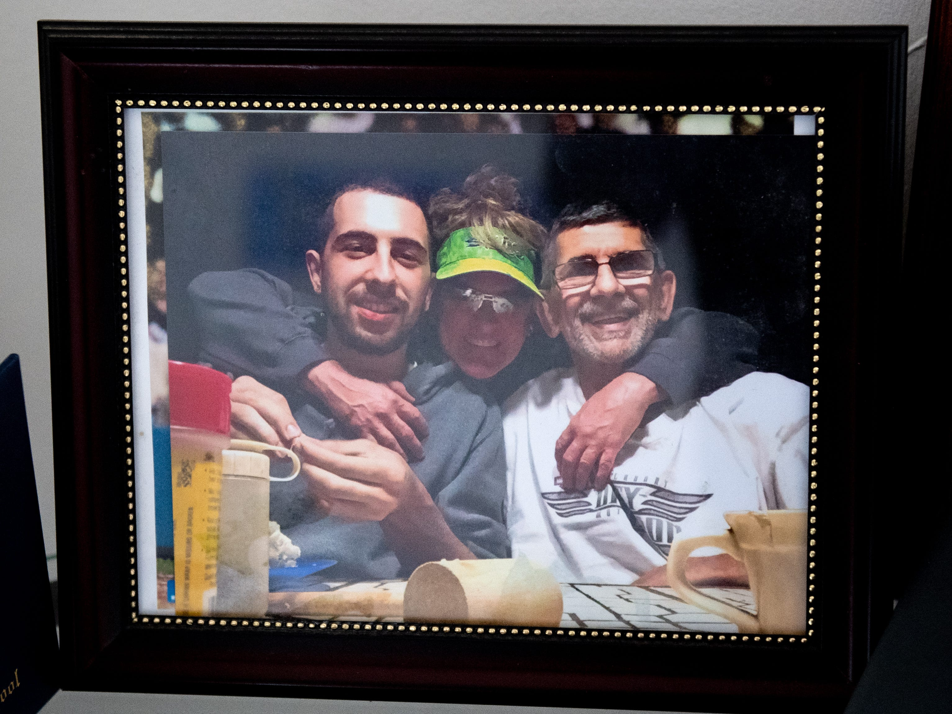 A picture of (left to right) Logan, Jamie and Tim Minnich sits on the desk in Logan's room, February 14, 2019.