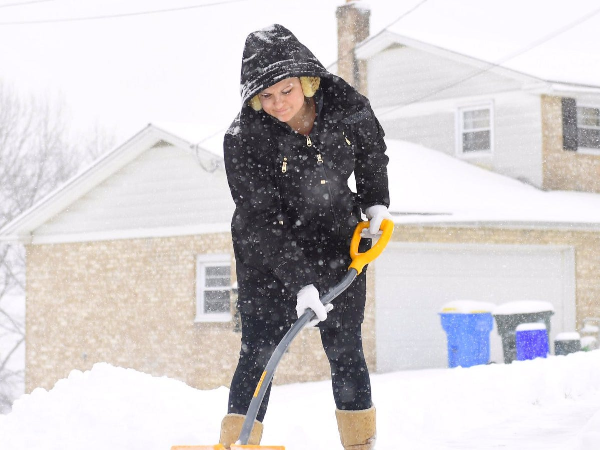 Yorkers like Tristanlyn Bixler-Kint clear their driveways as the snow slows down.