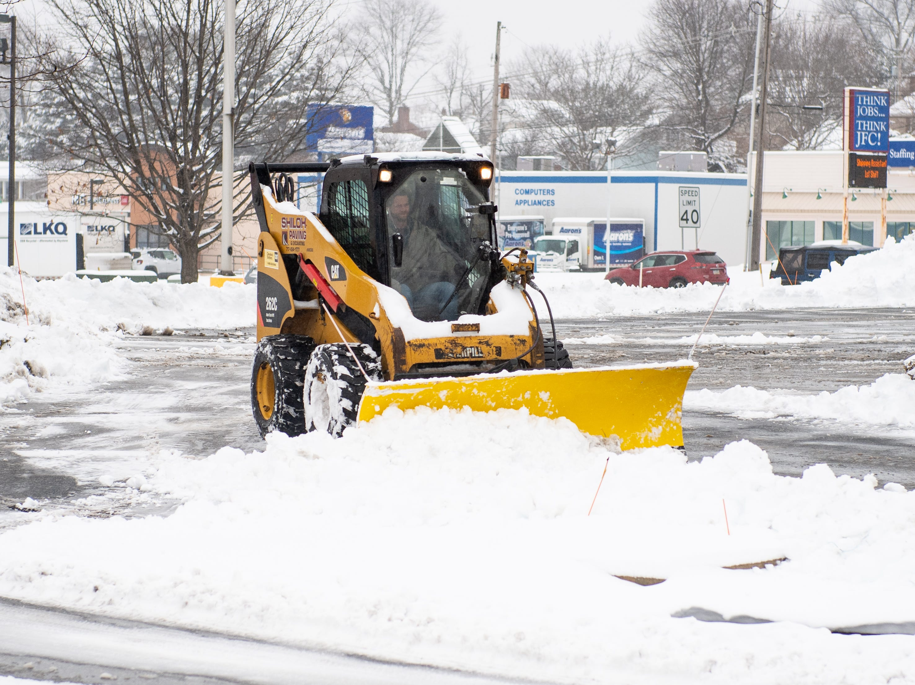 Small bulldozers work to clear parking lots in West Manchester Township as the snow turns to rain, February 20, 2019.