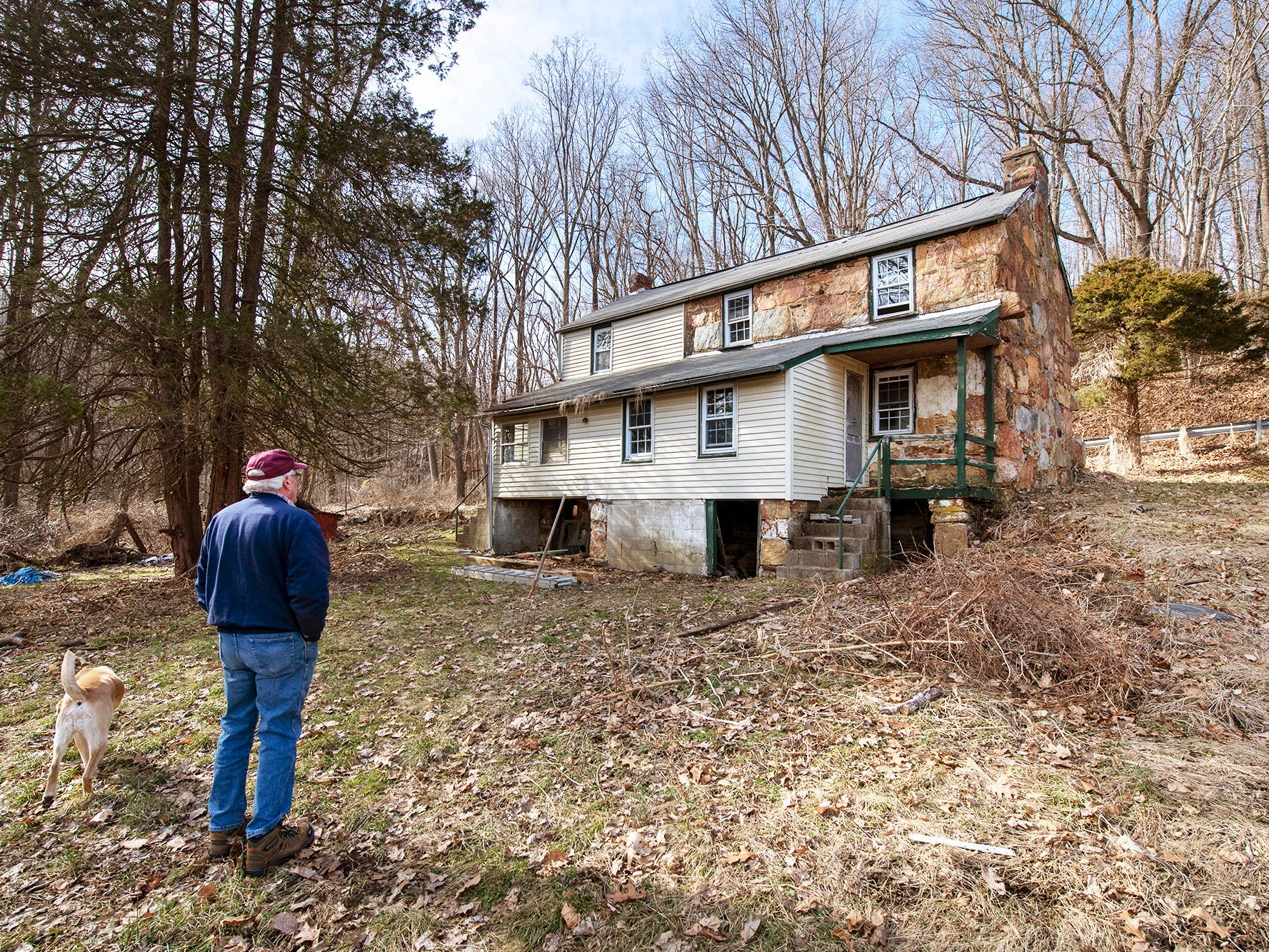 Old Line Museum volunteer Don Robinson and his dog Jake look at the rear of the newest welsh quarrymen's cottage in Coulsontown in Peach Bottom Township on February 19, 2019. Robinson put up some of his own money in combination with the museum when the cottage became available.