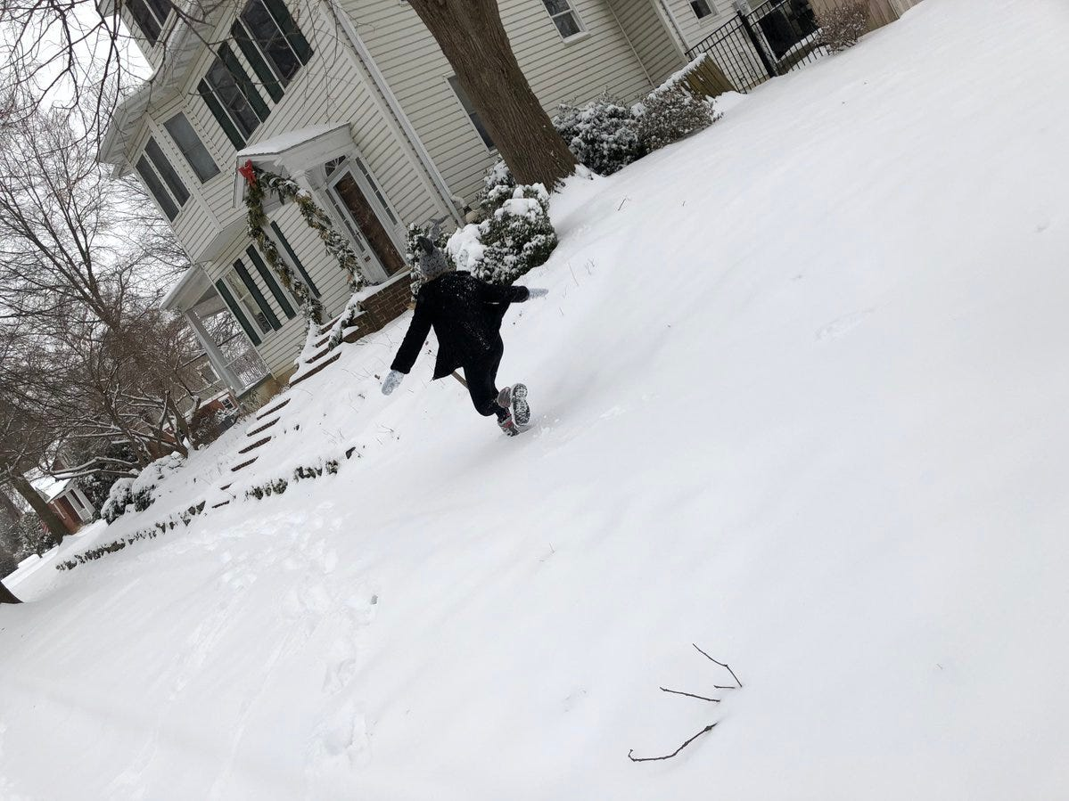 A child plays in the snow along the sidewalks in Camp Hill.
