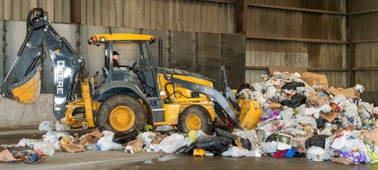 Transfer station attendant Dan England pushes trash into a large pile.