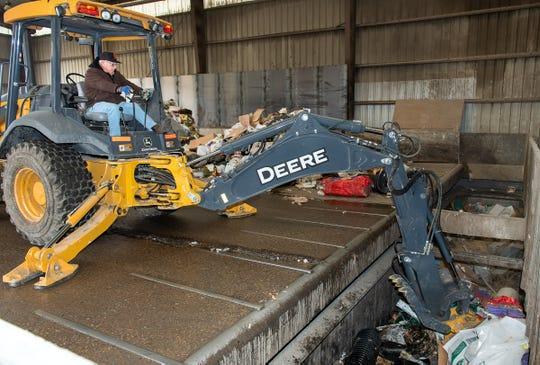 Dan England, attendant at the Yerington Transfer Station, packs trash into a truck.
