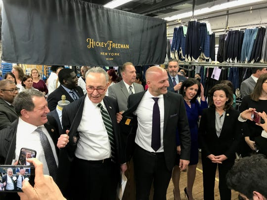 Rep. Joseph Morelle, U.S. Sen. Charles Schumer and Hickey Freeman's Stephen Granovsky show off the Hickey Freeman suit labels Wednesday after the announcement of an $8 million investment in the North Clinton Avenue factory.