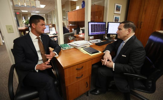 Todd Alexander, financial advisor at Brighton Securities, goes over a clientÕs plan with George T. Conboy, chairman at the financial services company.