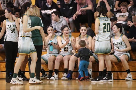 C.G. Finney girls basketball players Silvia Fioravanti (23) and Grace Martin (14) give high-fives to a young fan during introductions before a Section V high school girls basketball game against the Northstar Christian Academy Knights at C.G. Finney.