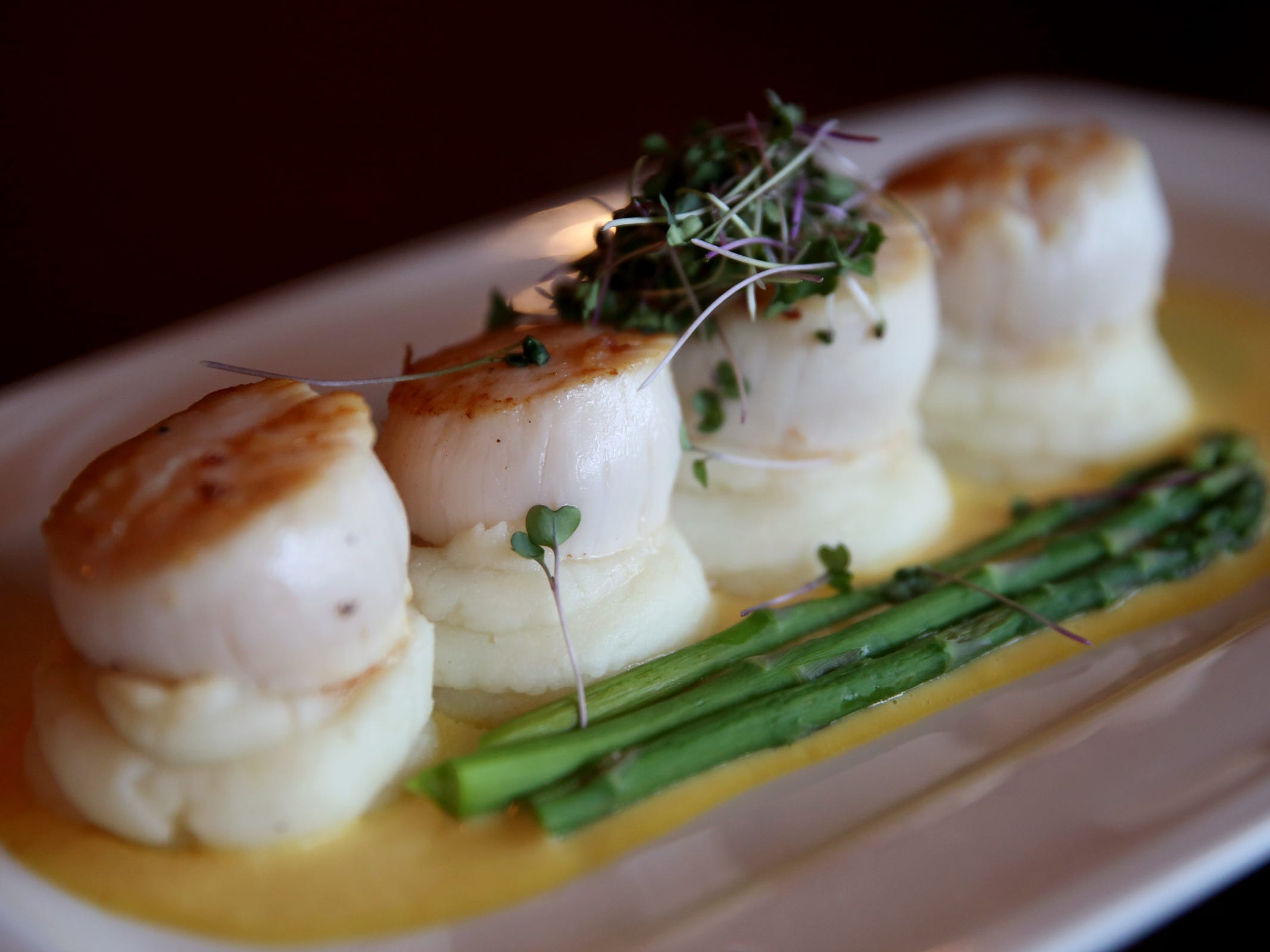 Seared scallops with mashed potatoes, saffron pineapple sauce and vegetables at Bentley's Grill in Salem on Friday, Feb. 15, 2019.