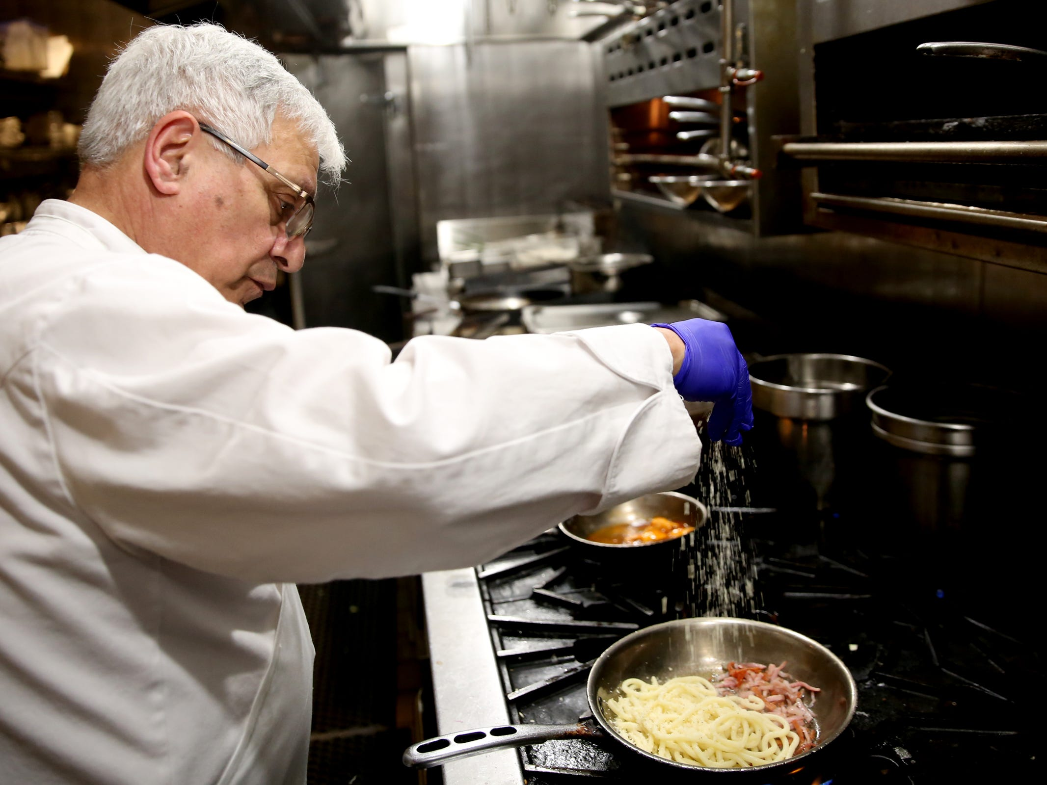Executive chef Hans Afshar adds parmesan to a carbonara pasta at Bentley's Grill in Salem on Friday, Feb. 15, 2019.