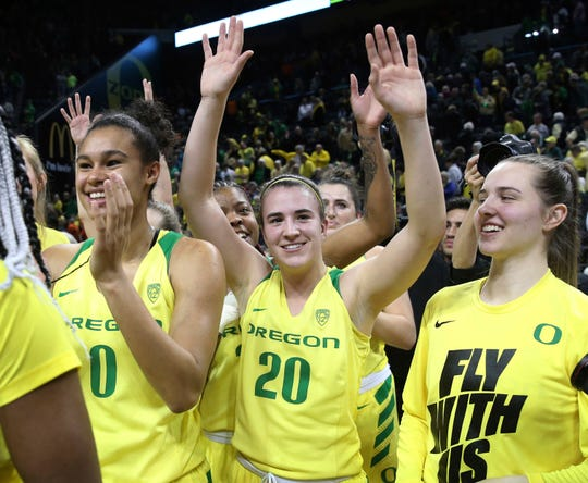 Oregon's Satou Sabally, left, Sabrina Ionescu and Morgan Yeager acknowledge fans after Oregon defeated Oregon State 77-68 in an NCAA college basketball game Friday, Feb. 15, 2019, in Eugene, Ore.