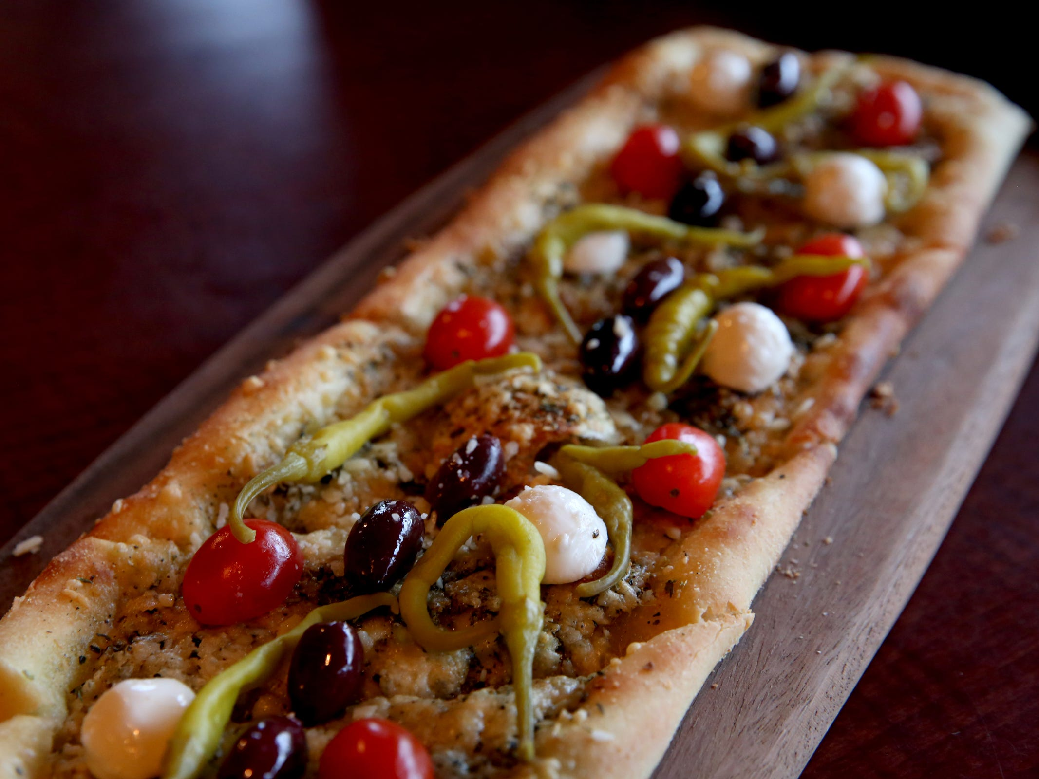 The Flat Herb Bread, with fresh roasted garlic, herbs, parmesan, cambozola cheese and cherry tomatoes at Bentley's Grill in Salem on Friday, Feb. 15, 2019.