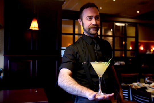 Head bartender Ethan Plumb balances a cocktail on the op of his hand at Bentley's Grill in Salem on Friday, Feb. 15, 2019.