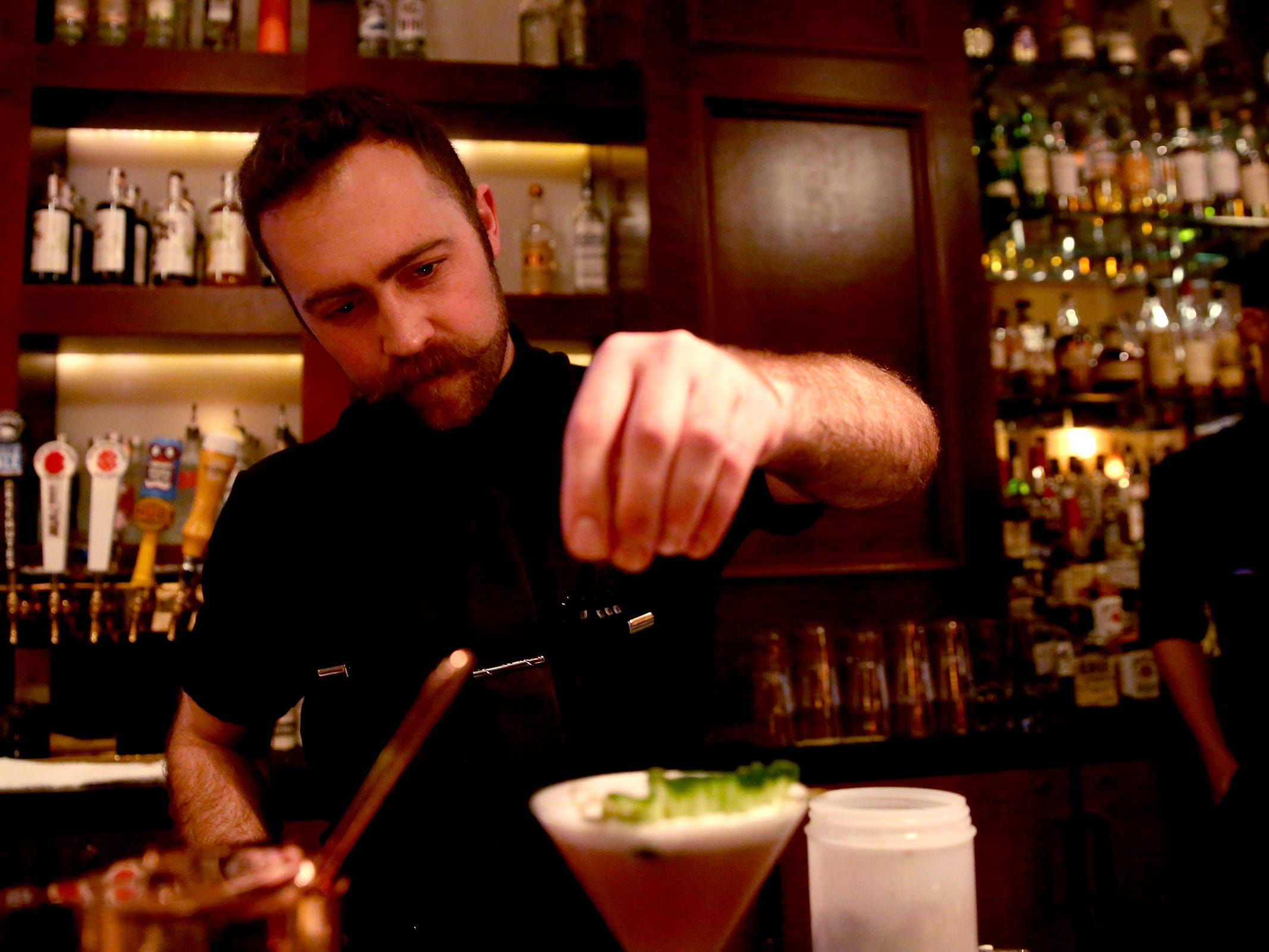 Head bartender Ethan Plumb makes a cocktail at Bentley's Grill in Salem on Friday, Feb. 15, 2019.