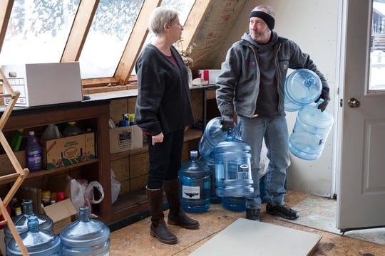 Catherine Maynard, a natural resource analyst for the U.S. Department of Agriculture, receives a bottled water delivery at her home in Rimini, Mont., by Bart Young of Big Spring Water on Feb. 18, 2019.