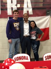 Sonora High School athletic director Jeff Cordell shows off Sonora's latest college sports signeees, Hunter Bunch (left) and Karah Martinez (right). Bunch will play football with Mary Hardin-Baylor while Martinez will play volleyball for Sul Ross State.