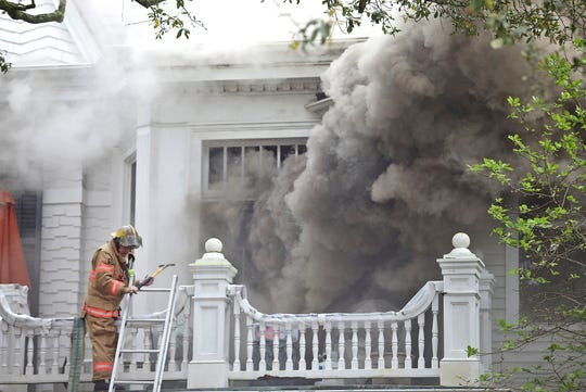Firefighters abandon a second-story balcony after heavy smoke erupts from a door as the New Orleans Fire Department battles a seven-alarm fire at the historic Morris-Downman House at 2525 St. Charles Avenue in New Orleans on Wednesday, February 20, 2019.