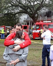 People console one another while a seven-alarm fire at the historic Morris-Downman House at 2525 St. Charles Avenue in New Orleans escalates on Wednesday, February 20, 2019.