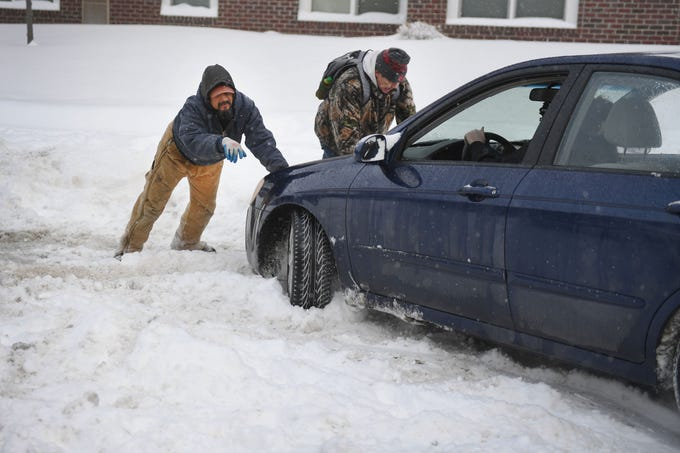 Tony Roman, left, and Roger Arpan, right, help a woman get her car unstuck Wednesday, Feb. 20, in Sioux Falls. According to the Sioux Falls national weather service the Sioux Falls airport was at 7.6 inches as of 10:12 a.m.