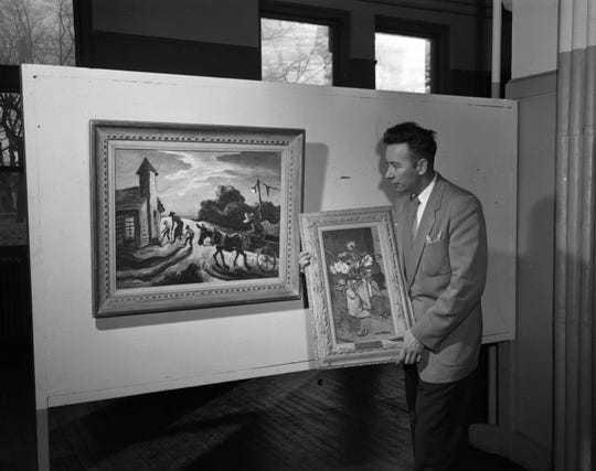 "Springfield Art Museum's third director, Kenneth Shuck, is shown on Dec. 14, 1954 at city hall, where art was displayed before the museum moved to its current location in Phelps Grove Park in 1958. At left is ""Prayer Meeting"" by Thomas Hart Benton; Shuck is holding ""Still Live with Ground Pine"" by Eugene R. Witten."