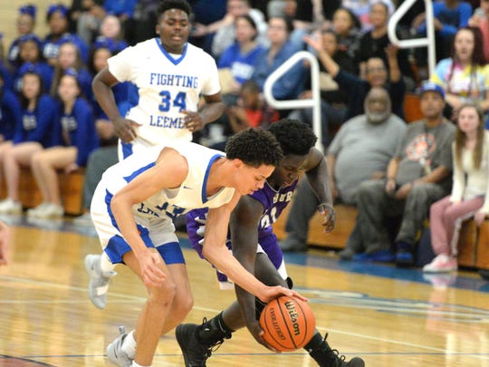 Lee High's Darrion Simms and Strasburg's Da'Neil Holliday battle for the ball Tuesday in the Region 2B boys basketball quarterfinals.