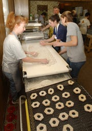 Tammy Smith, left, Elizabeth Botkin and Katie Perdue make donuts at the Puffenbarger Sugar Camp Saturday during the Highland County Maple Festival in 2003.