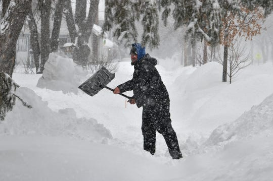 Corey Decker clears his driveway as snow continues to fall Wednesday, Feb. 20, in St. Cloud.