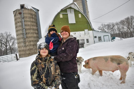 Brenda Rudolph poses for a photograph with her children, Everett and Vivian, and pig, Hans, Wednesday, Feb. 20, on their farm near Little Falls.