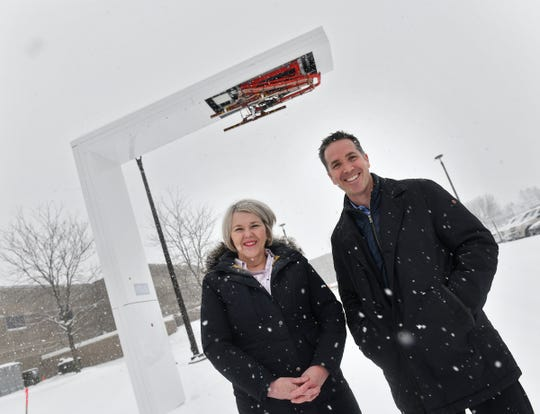 New Flyer of America President Chris Stoddart and Manufacturing and Facilities Senior Vice President Margaret Lewis stand near an electrical bus charging station Wednesday, Feb. 20, at the company's manufacturing facility in St. Cloud.