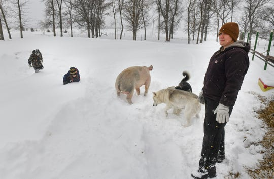 Brenda Rudolph watches as her children play in the snow Wednesday, Feb. 20, on their farm near Little Falls.
