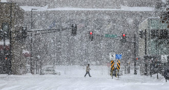A pedestrian crosses the street near the Stearns County Courthouse as heavy snow falls in the late morning Wednesday, Feb. 20, in St. Cloud.