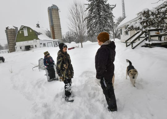 Brenda Rudolph watches as her children Everett and Vivian enjoy some time in the snow Wednesday, Feb. 20, on their farm near Little Falls.