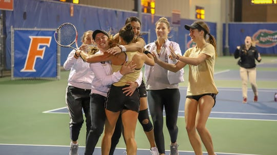 FSU tennis players celebrate their win over Florida Tuesday night.