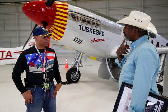 Alexander Brickler talks with Coach Macon, the son of a World War II army infantryman whose career was impacted by segregation in the armed forces, about the P-51 C Mustang plane, flown by the Tuskegee Airmen in World War II on display in the Flightline hangar at the Tallahassee International Airport as part of the RISE ABOVE: Red Tail Traveling Exhibit.
