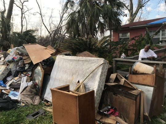 James Fennell looks over the pile of debris outside his house on Avenue A in the historically black Millview subdivision in North Port St. Joe.