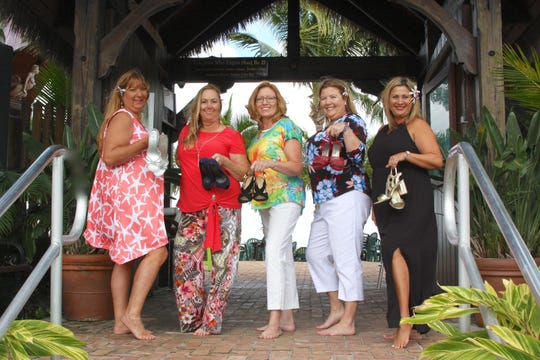 Port St. Lucie Business Women's Fashion Show committee members Michele Backus, Donna Mulvey, Melissa Winstead, Devon Dwyer and Diana Gonzalez show off their Hawaiian heels.